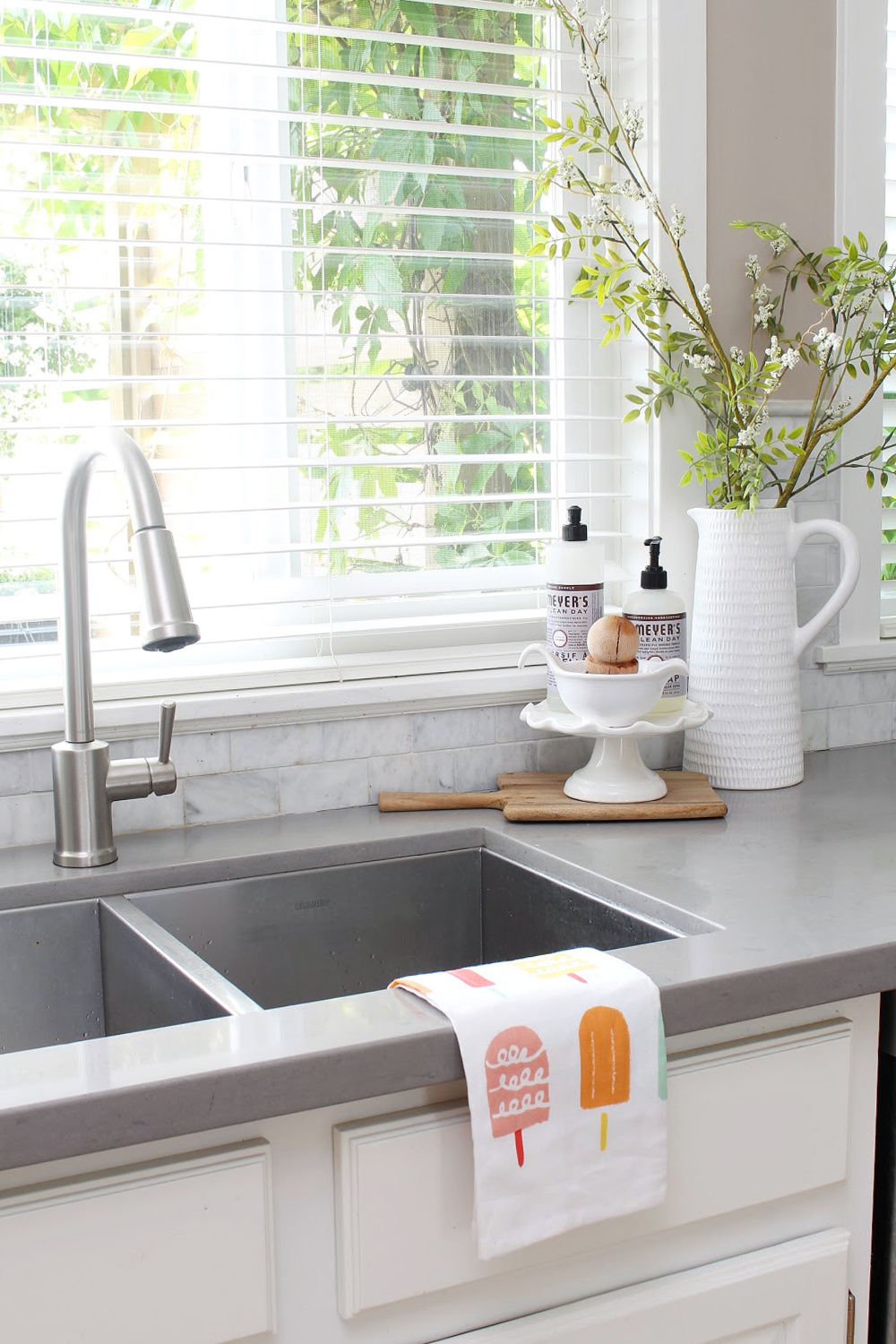 Kitchen sink decorated for summer with popsicle kitchen towel and cake stand.