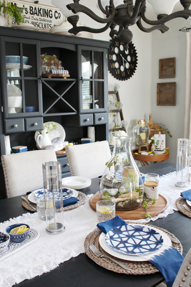 Summer dining room with a painted black table, buffet and hutch decorated with blues.