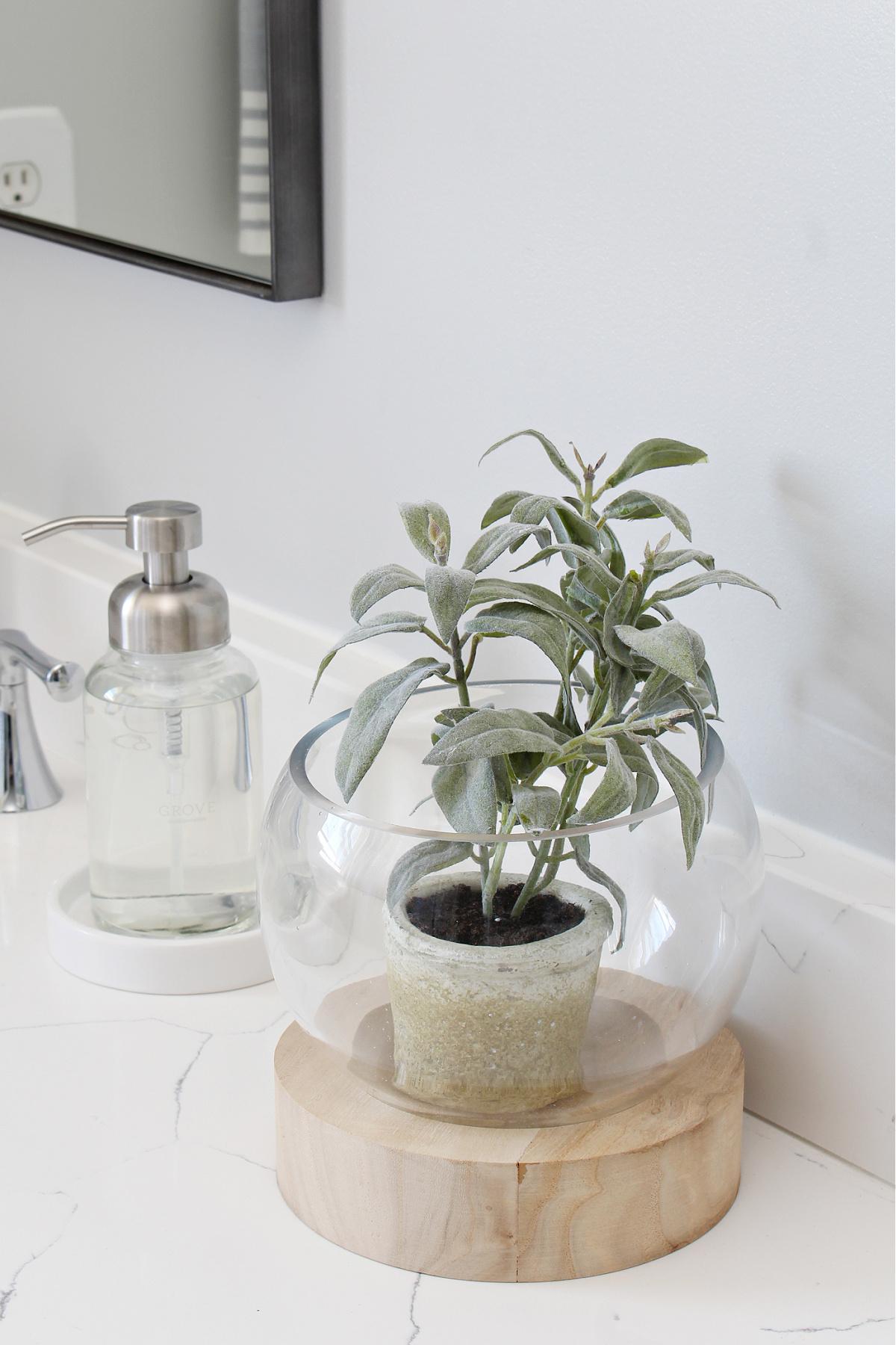 White quartz bathroom countertop with hand soap dispenser and glass plant holder.