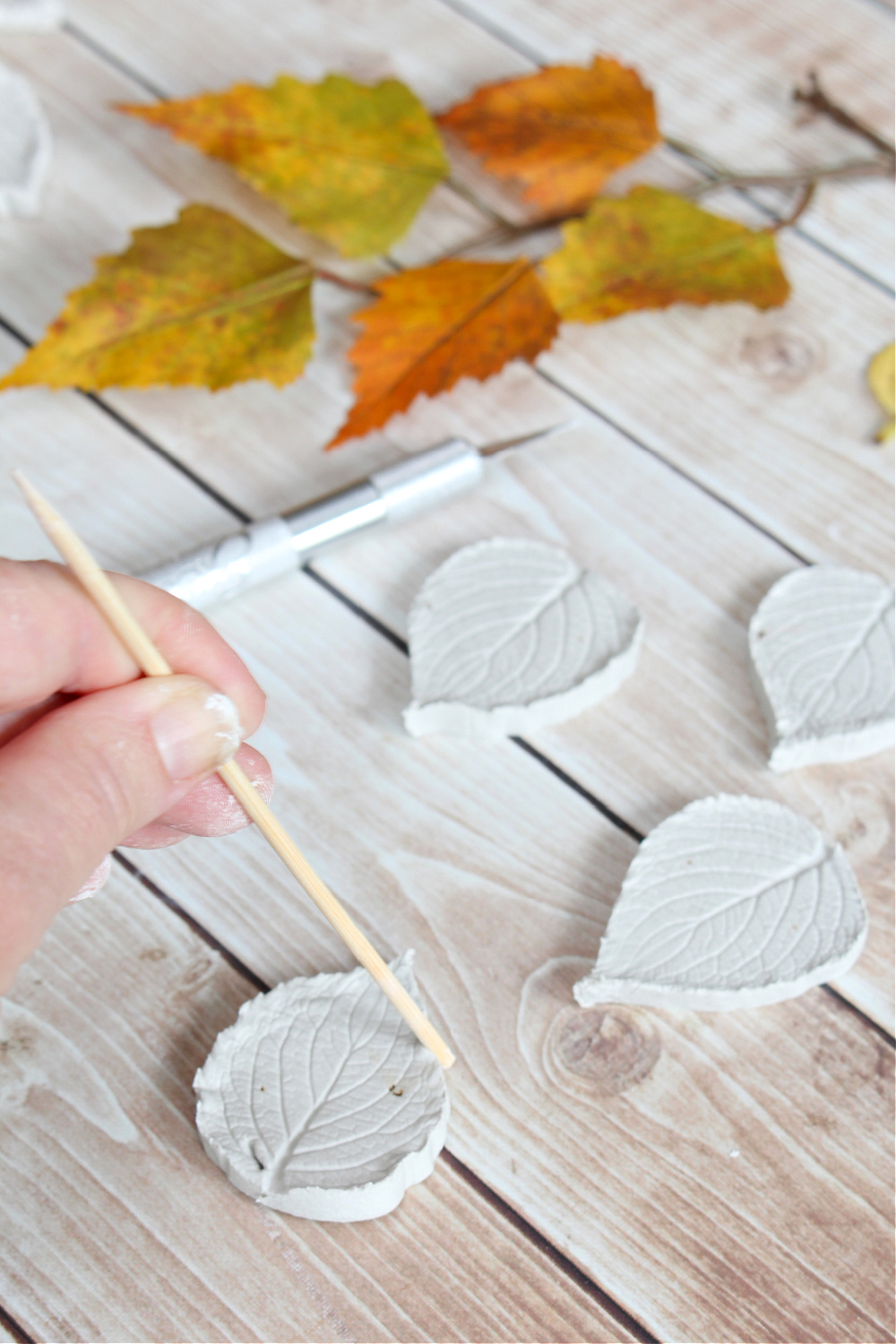 Molding air dry clay leaves with a wood skewer.