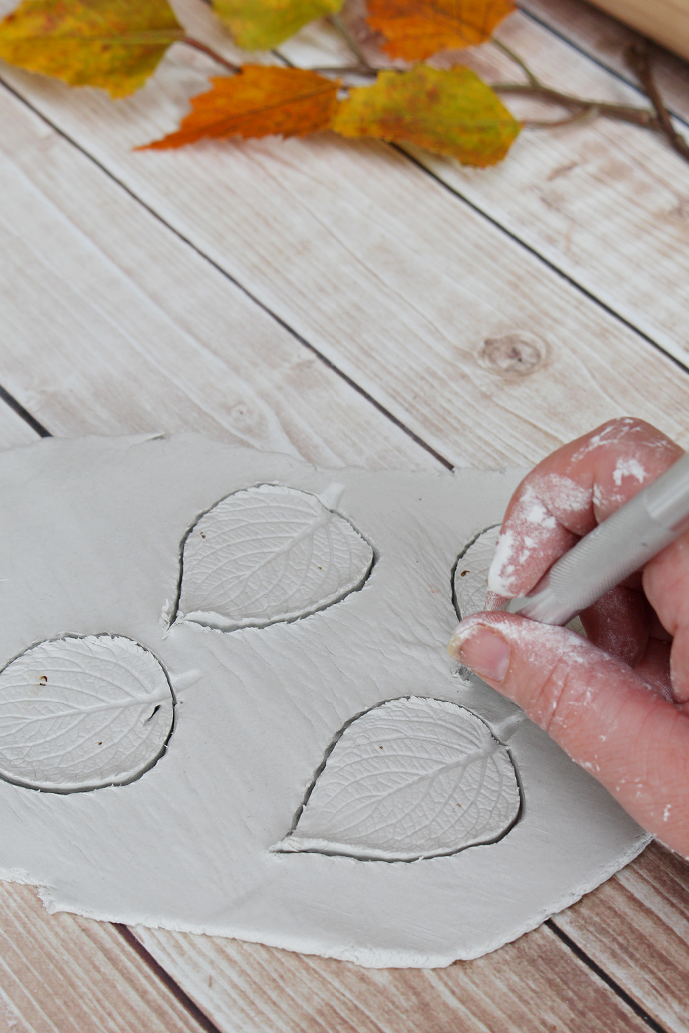 Air dry clay leaves being cut with an exacto knife.