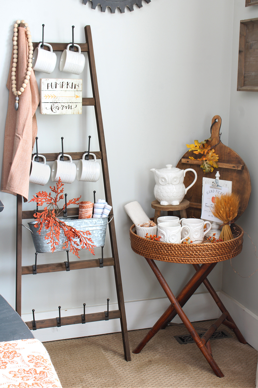 Hot beverage bar with owl mugs and a rustic mug ladder.