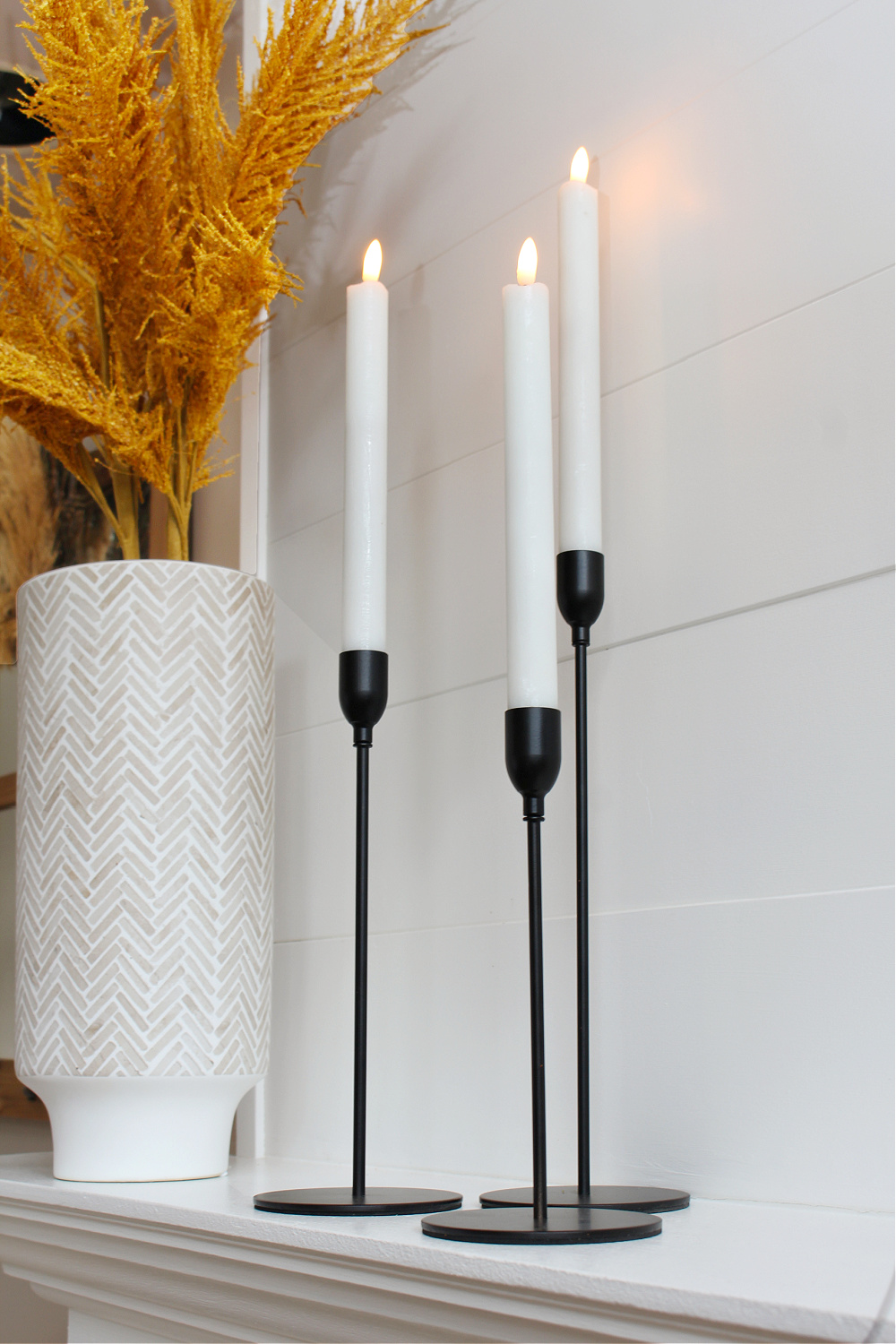 Black metal taper candle holders on a fall mantel.