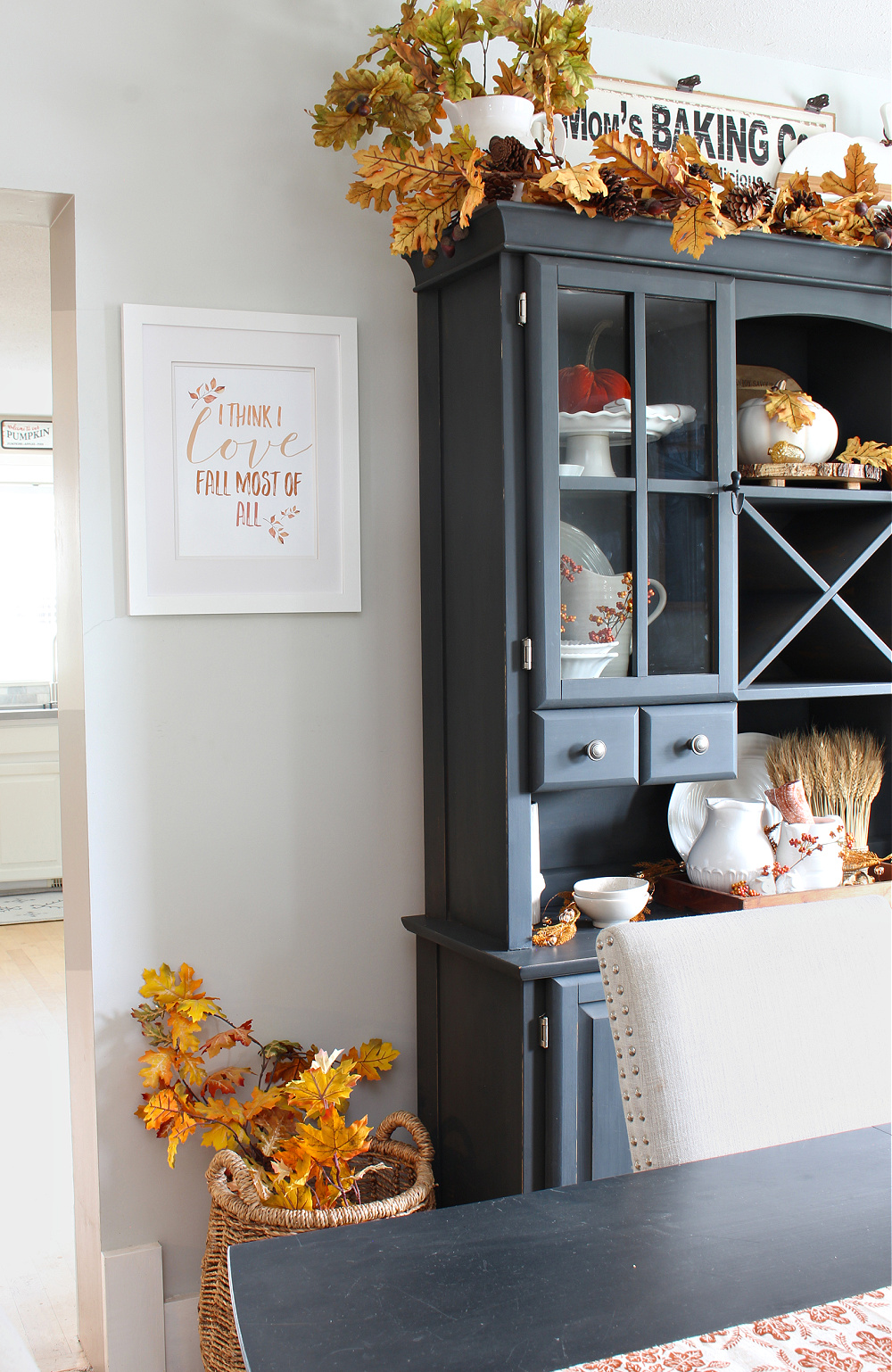 I Think I Love Fall Most of All free printable hanging in a white frame in a dining room.
