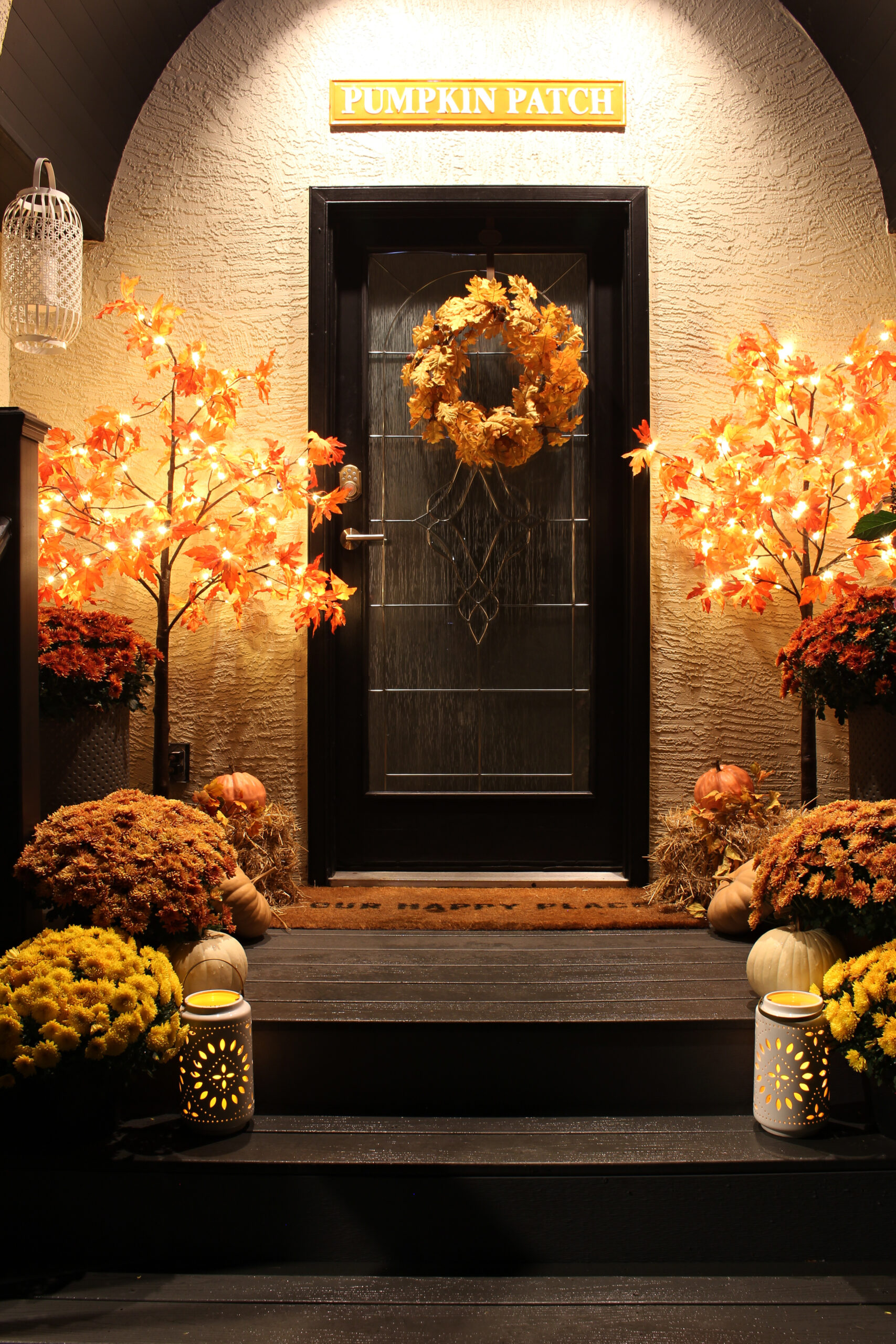 Glowing fall front porch at night with a lighted fall tree and candles.