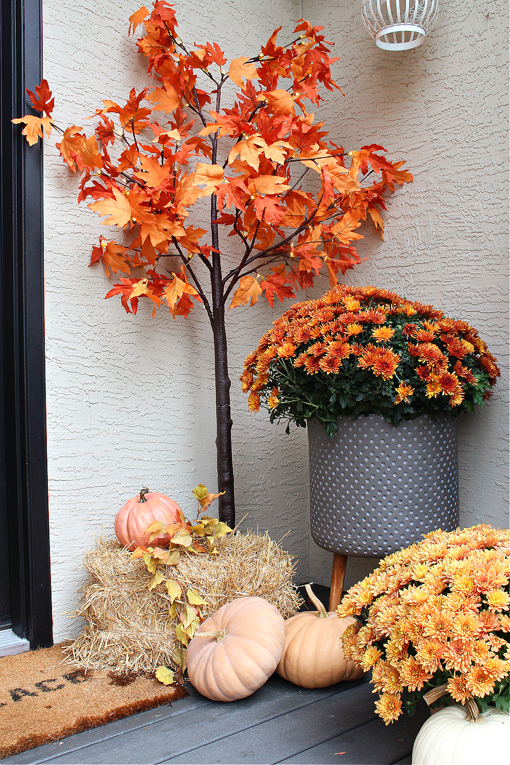 Fall front porch with mums, pumpkins, and hay.