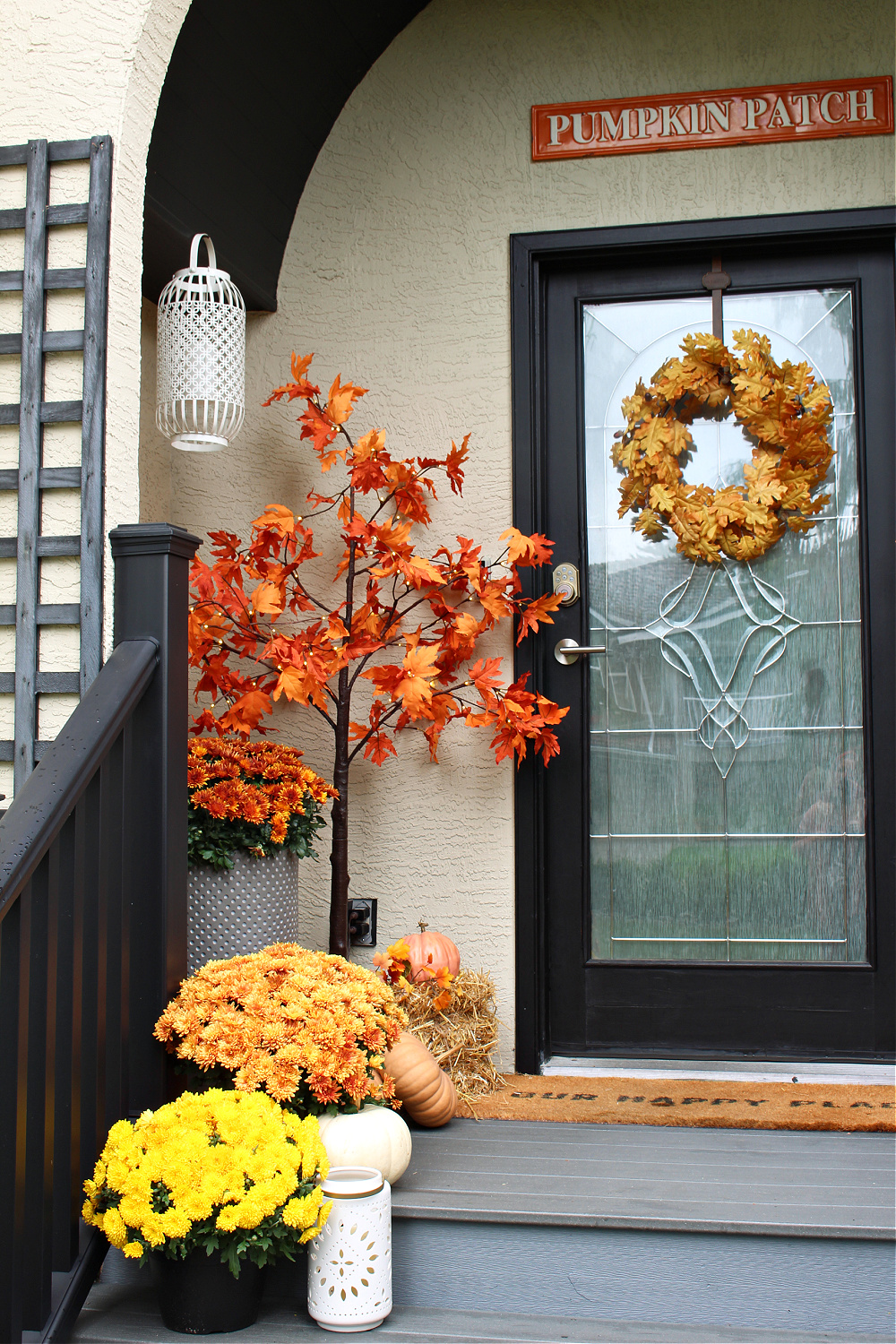 Fall front porch decorated for fall with mums and lighted trees.