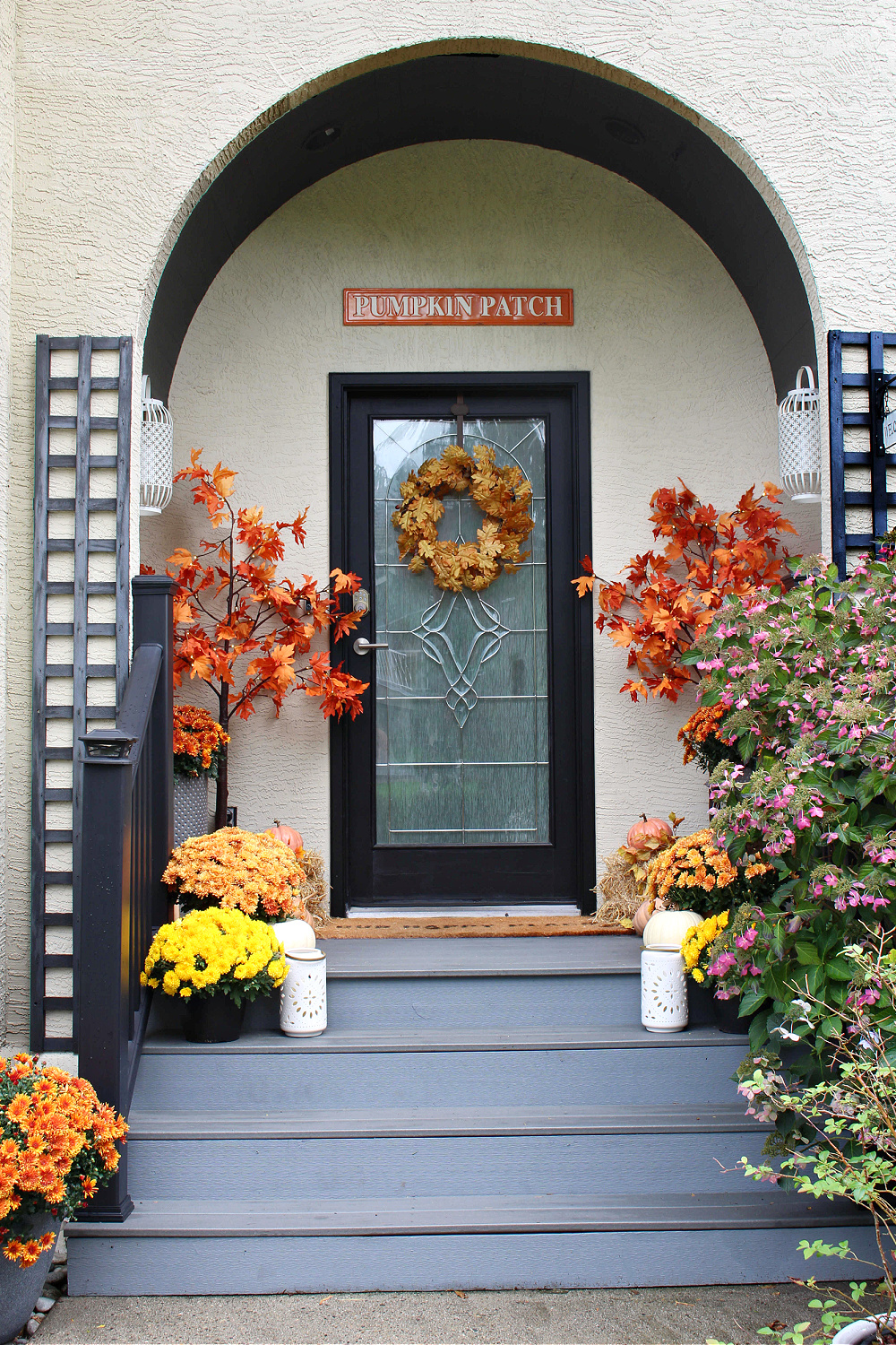 Fall front porch decorated with mums, pumpkins and lighted trees.