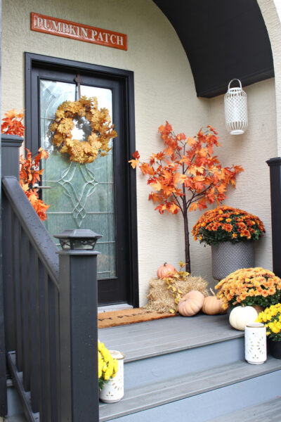 Fall front porch decorated with traditional fall colors.