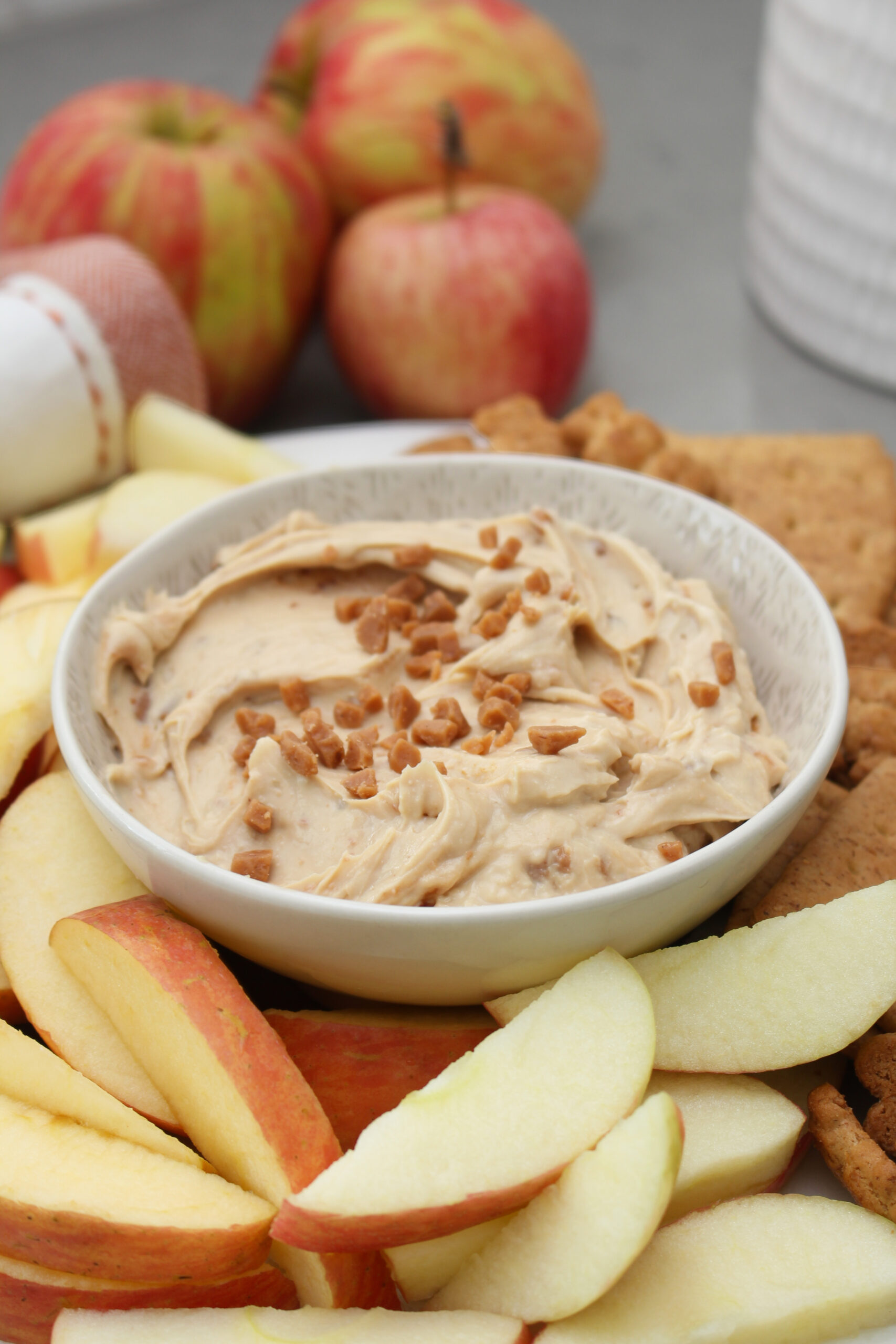 Cream cheese apple dip on a plate with apples and graham crackers.