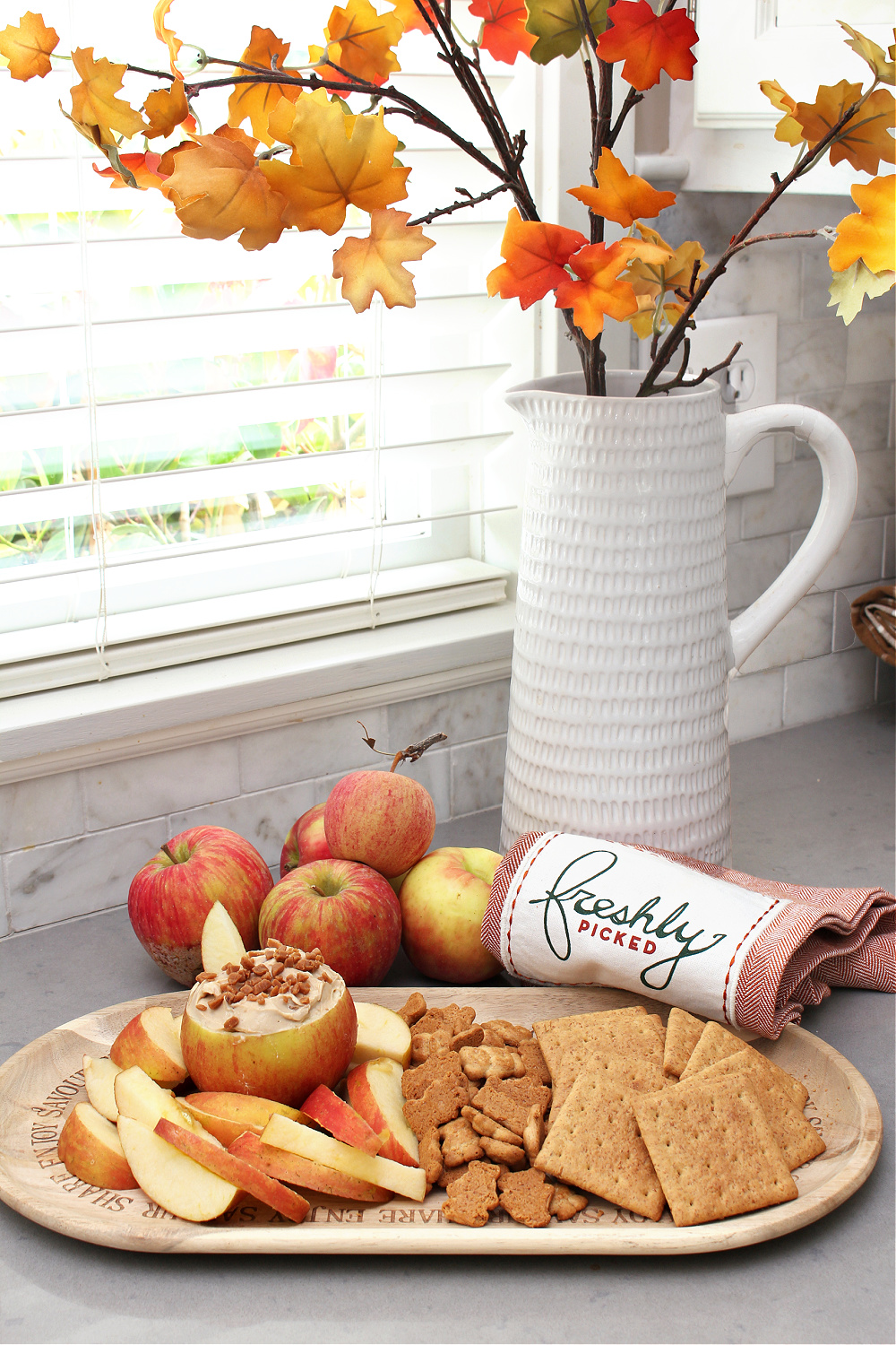 Cream cheese apple dip in an apple bowl with apples and graham crackers.