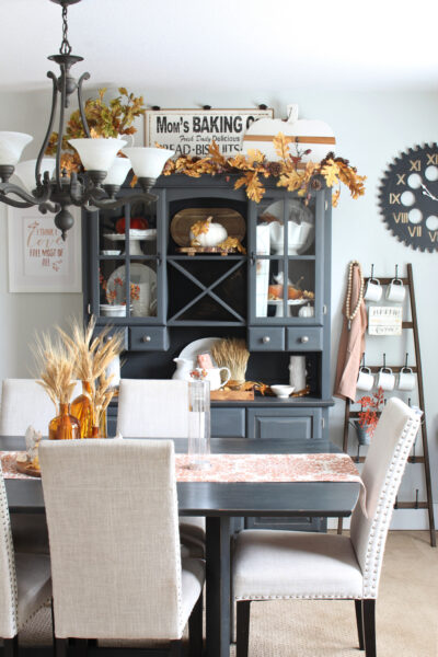 Traditional fall decor colors in a dining room with painted black table and hutch.