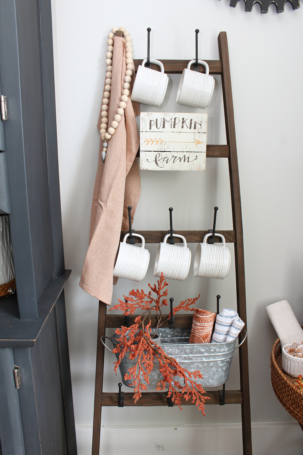 Rustic mug ladder decorated for fall.