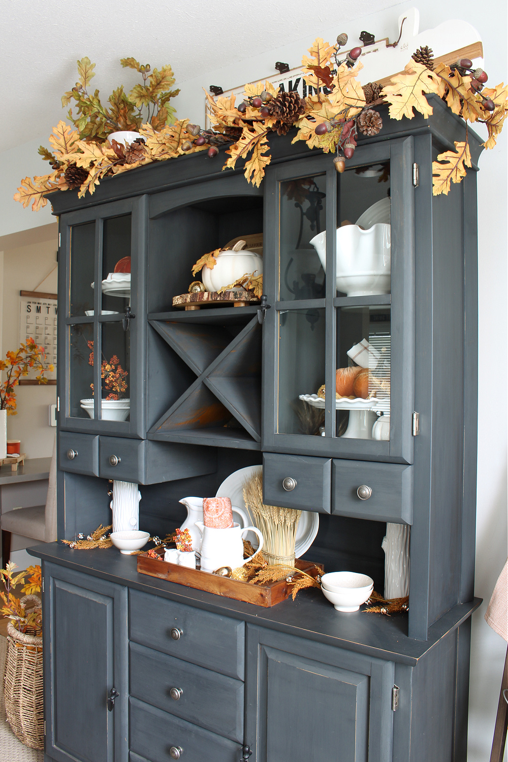 Black painted hutch decorated for fall with traditional fall colors.