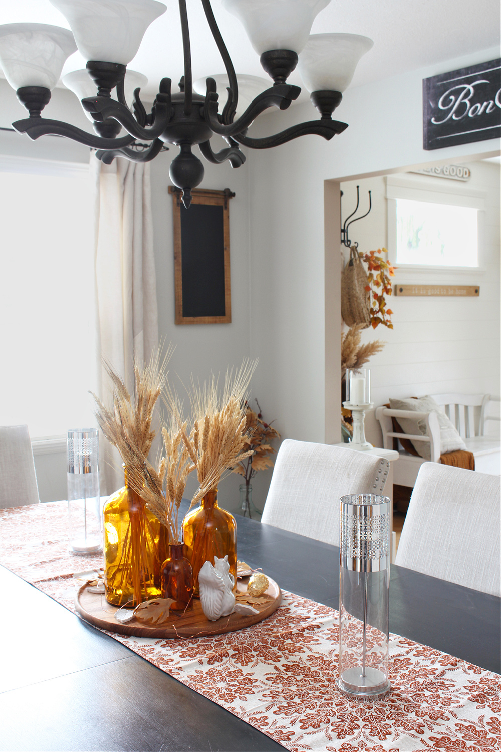 Amber glass fall centerpiece in a dining room decorated in traditional fall colors.