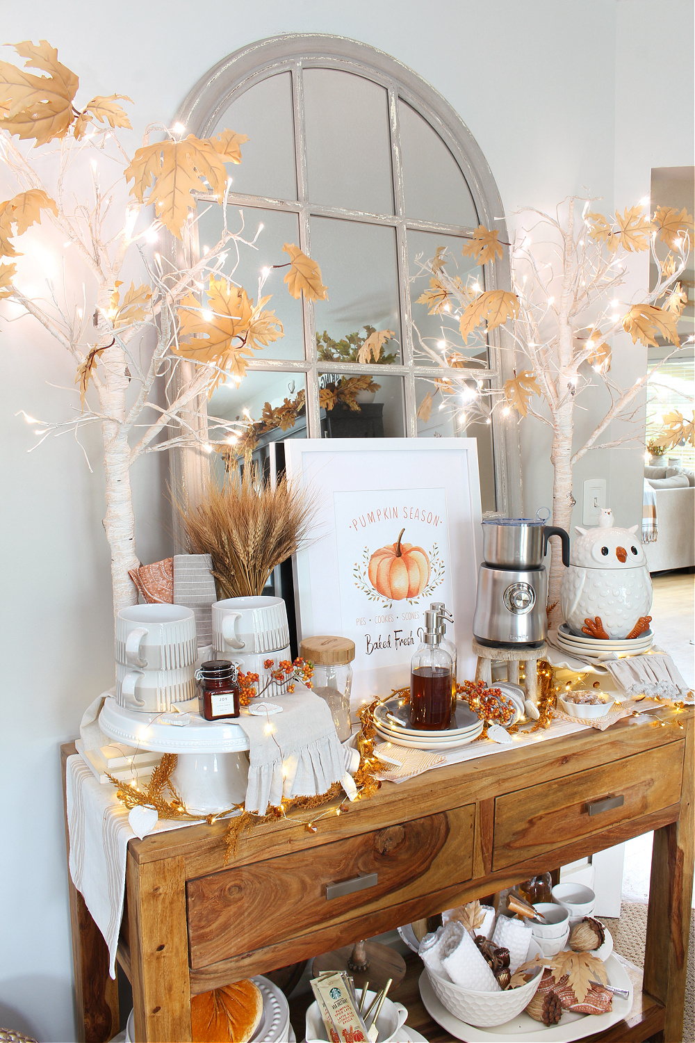 Fall coffee bar decorated with twinkle lights and lighted trees.