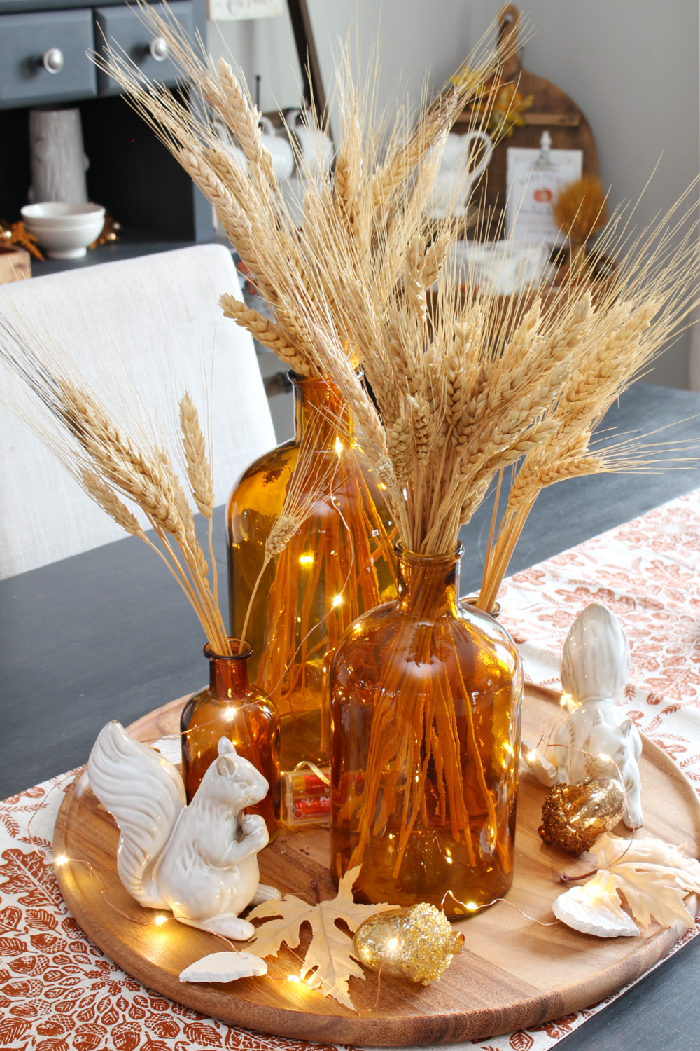 Fall nature-inspired centerpiece with glass amber bottles and twinkle lights.