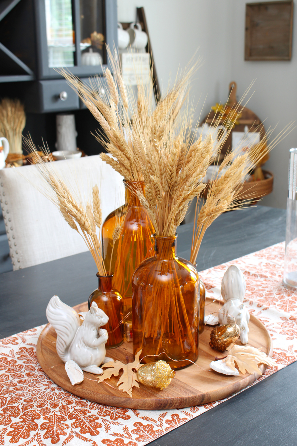 Fall centerpiece with amber glass bottles, wheat, and twinkle lights.