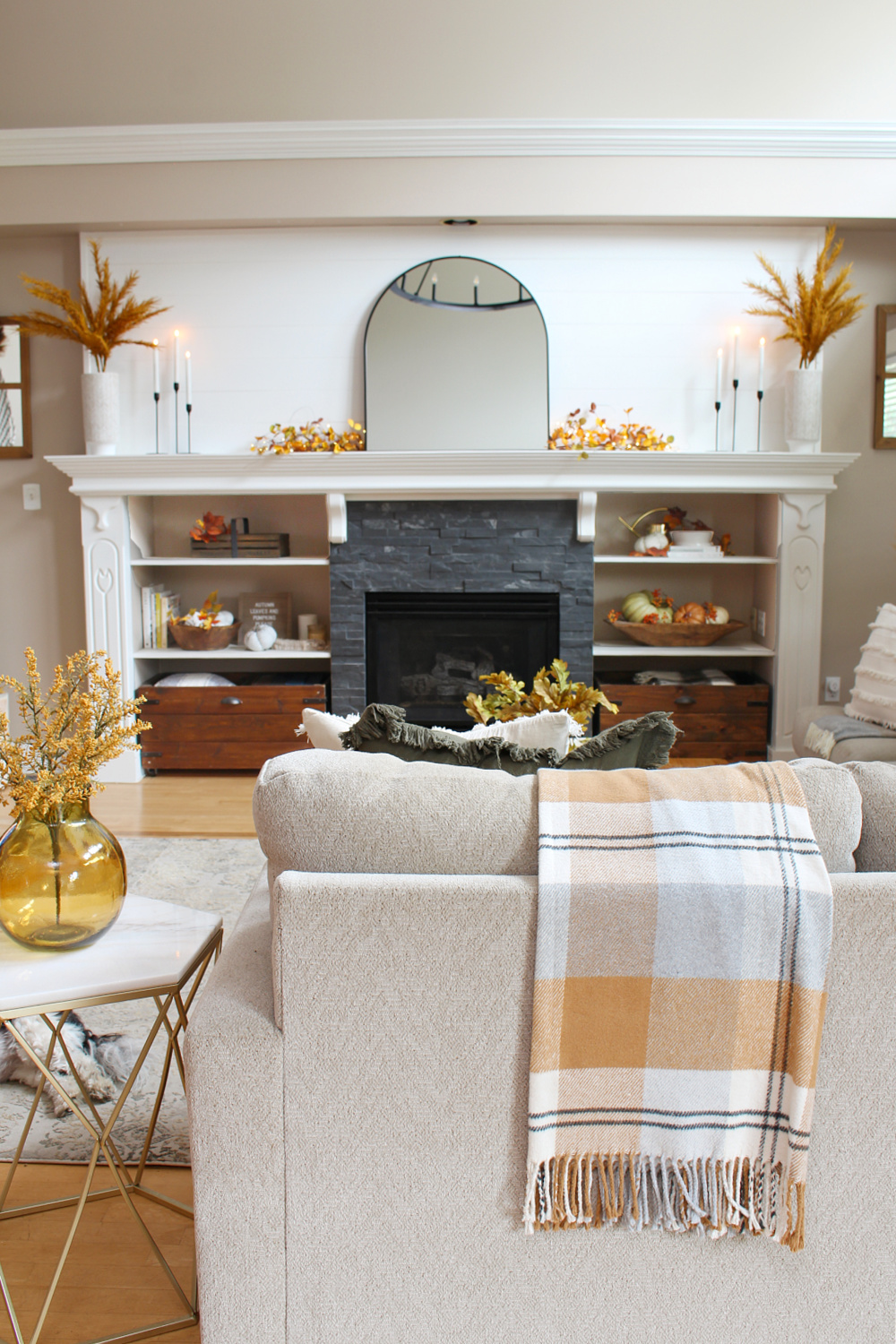 Fall mantel in a living room decorated for fall in traditional fall colors.