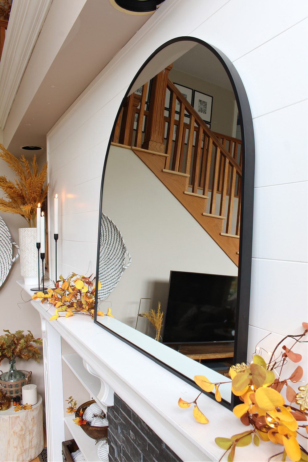 Black arched mirror on a fall mantel.