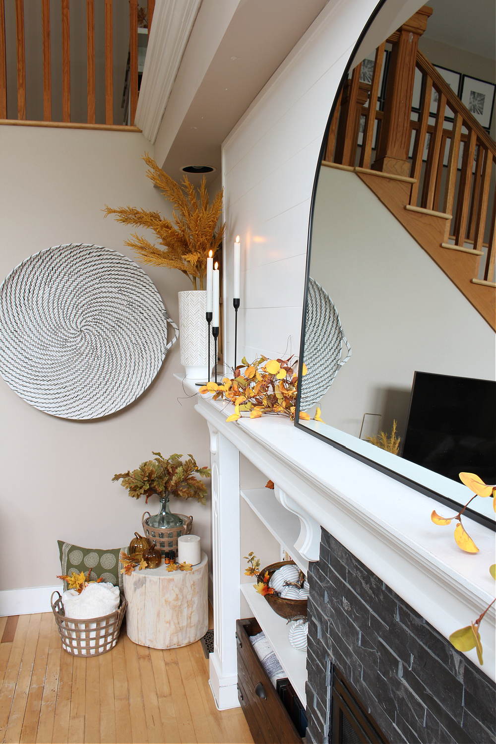 White mantel decorated for fall with black arched mirror.