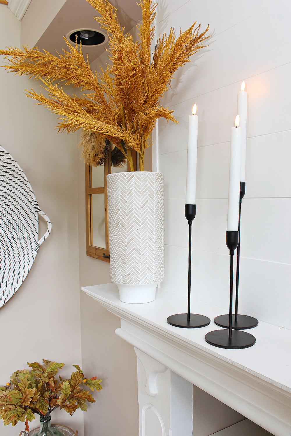 Black metal taper candle holders and orange pampas grass on a fall mantel.