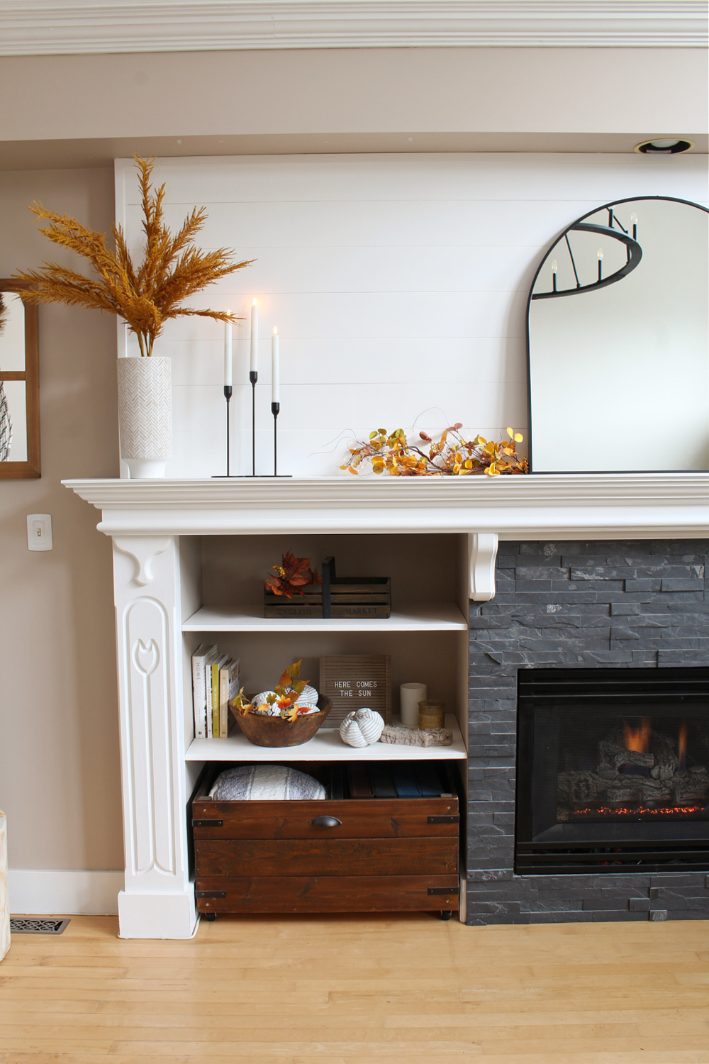White mantel with black stone fireplace surround decorated for fall.